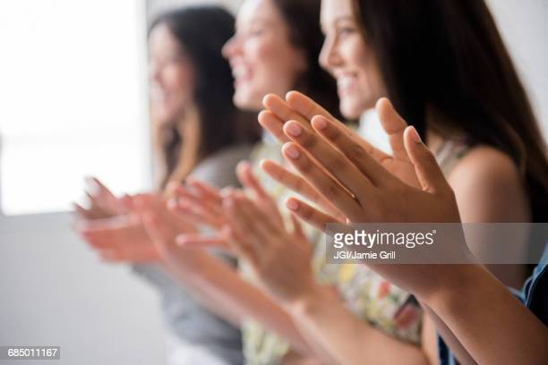 Smiling women applauding