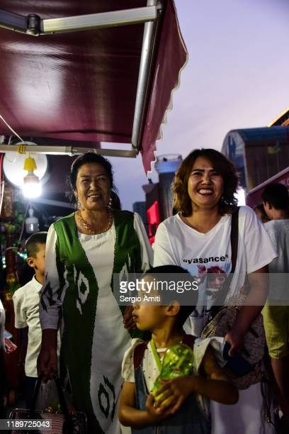 smiling women at a night market in urumqi - sergio amiti stock pictures, royalty-free photos & images