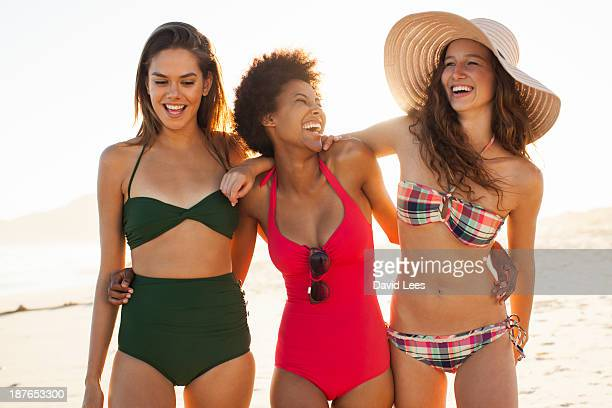 smiling women at beach - badkleding stockfoto's en -beelden
