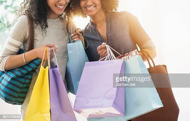 Smiling women carrying shopping bags