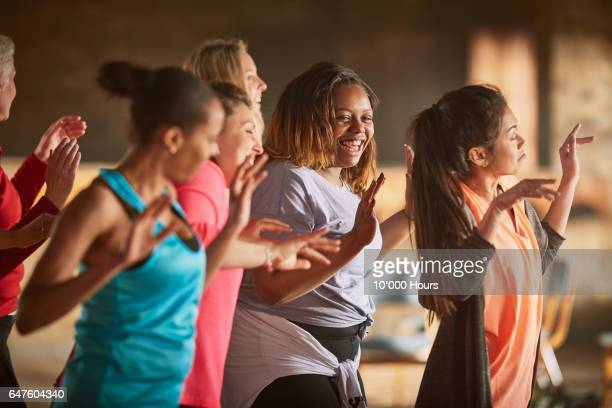 Smiling women dancing in gym.