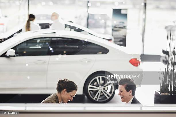 Smiling women discussing by car at showroom