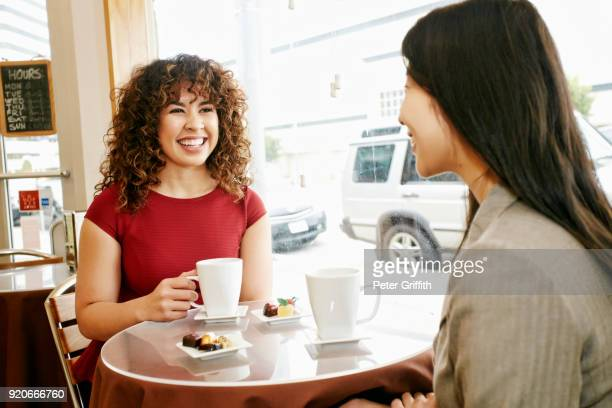 Smiling women drinking coffee and eating chocolates