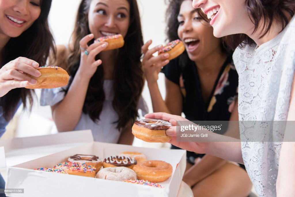 Smiling women eating donuts : Stock Photo