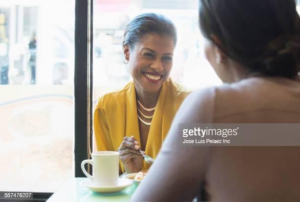Smiling women enjoying cake and coffee in cafe