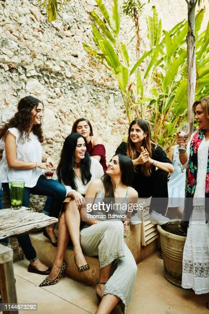 smiling women from multigenerational family hanging out in backyard during dinner party - nosotroscollection stockfoto's en -beelden