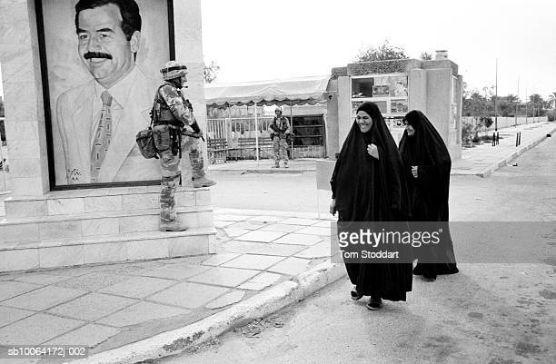 , Smiling women greet a Royal Marine Commando near a Saddam Hussein mural on the day Basrah was liberated.