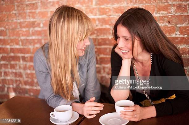 Smiling women having coffee in cafe