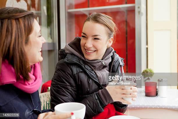 Smiling women having coffee outdoors