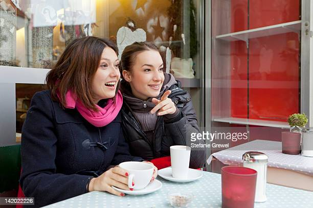 Smiling women having coffee outdoors