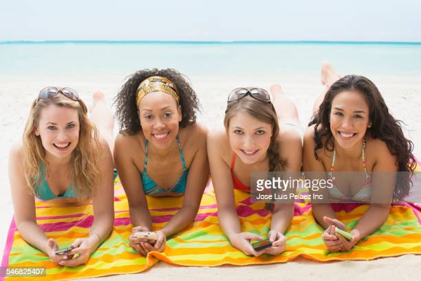 Smiling women holding cell phones on beach