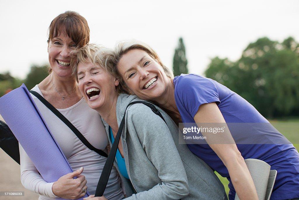 Smiling women holding yoga mats : Stock Photo
