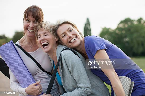 smiling women holding yoga mats - older woman stock pictures, royalty-free photos & images