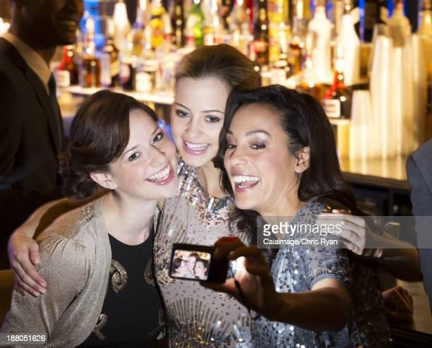 Smiling women hugging and taking self-portrait in nightclub