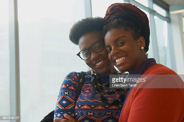 Smiling women hugging indoors