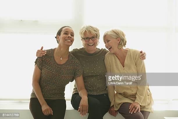 Smiling women hugging on bench