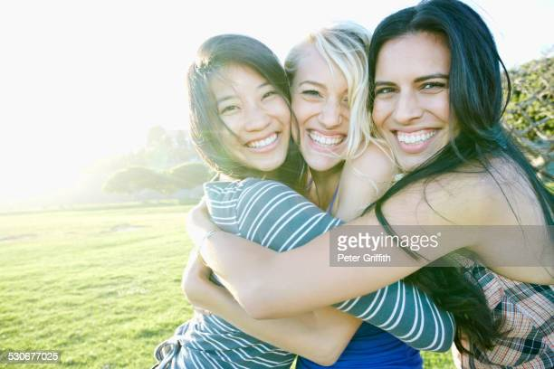 Smiling women hugging outdoors