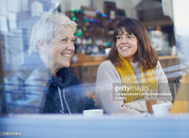 smiling women in cafe - talking stock pictures, royalty-free photos & images