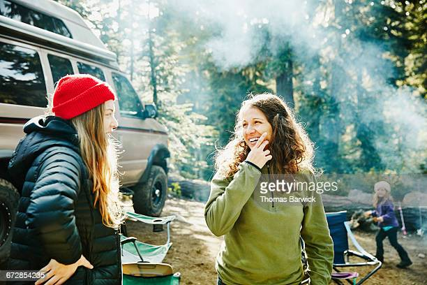 Smiling women in discussion while camping in woods