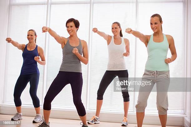 sonriente mujer en clase de ejercicio - defensa propia fotografías e imágenes de stock
