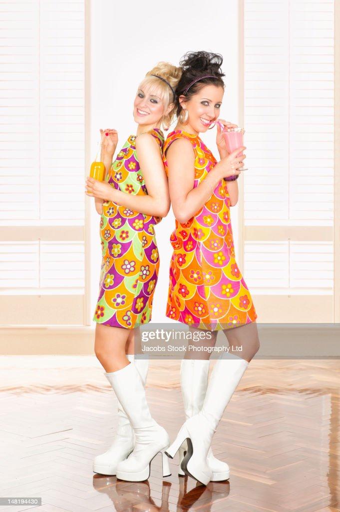 Smiling women in nostalgic dresses drinking : Stock Photo