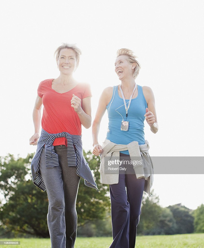 Smiling women jogging together : Stock Photo