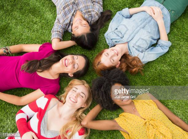 Smiling women laying in grass together