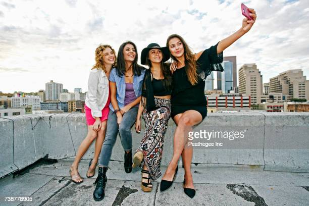smiling women posing for cell phone selfie on urban rooftop - four people stock pictures, royalty-free photos & images