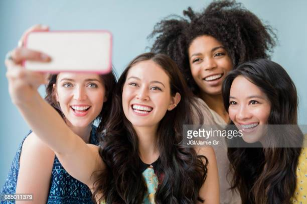smiling women posing for cell phone selfie - adults only stock pictures, royalty-free photos & images