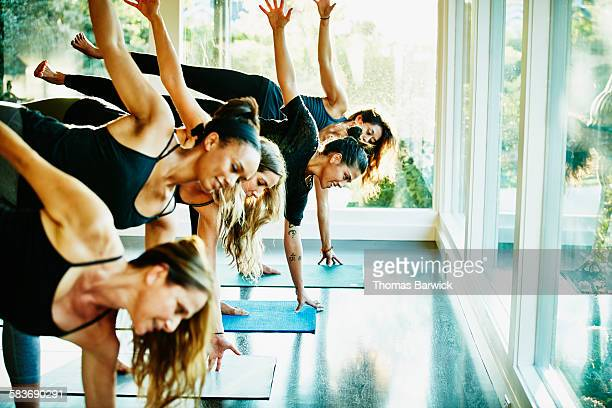 Smiling women practicing yoga in half moon pose