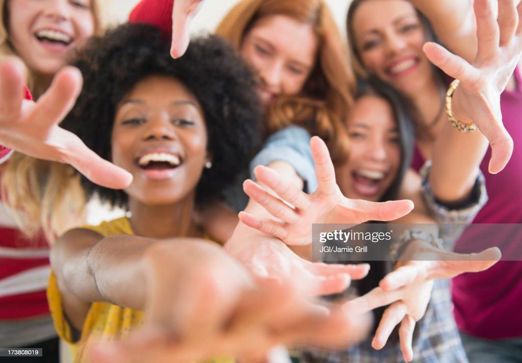 Smiling women reaching forward : Stock Photo