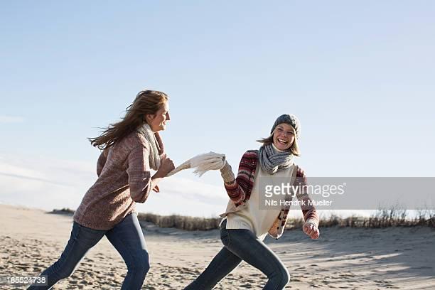 smiling women running on beach - 追いかける ストックフォトと画像