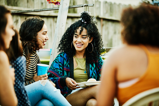 Smiling women sharing food and drinks during backyard barbecue - gettyimageskorea