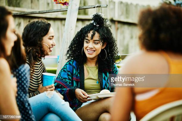 smiling women sharing food and drinks during backyard barbecue - topknot stock pictures, royalty-free photos & images