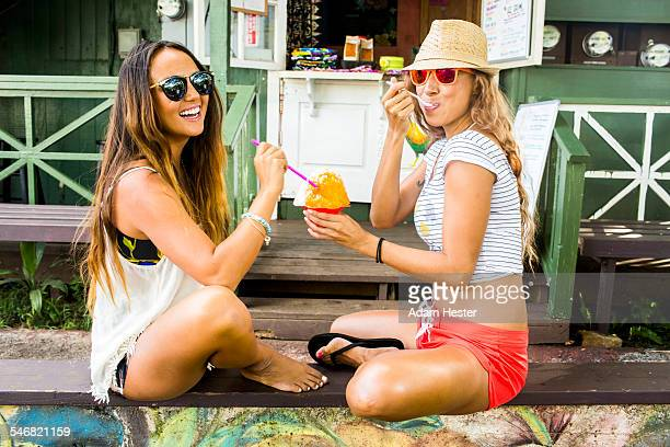 Smiling women sharing shaved ice
