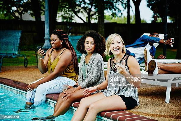 Smiling women sitting on edge of pool during party