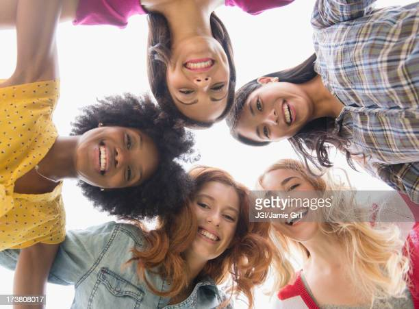smiling women standing in circle - multiculturalism stock pictures, royalty-free photos & images