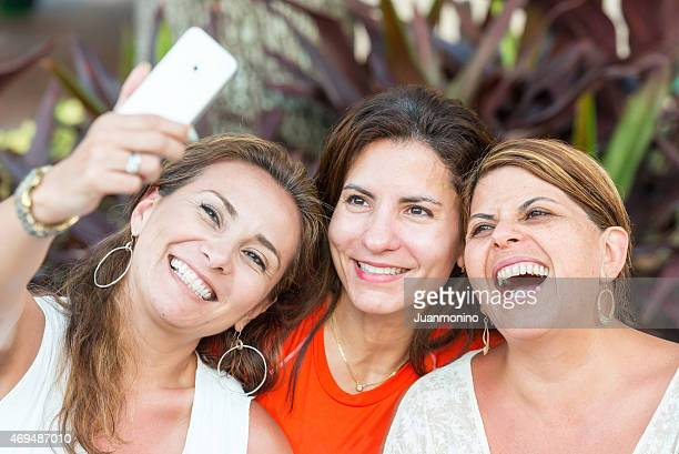 Smiling women taking a photo of themselves with phone