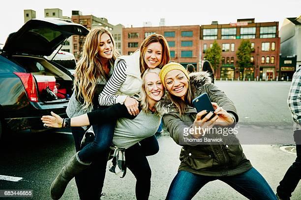 smiling women taking selfie at tailgating party - landvoertuig stockfoto's en -beelden