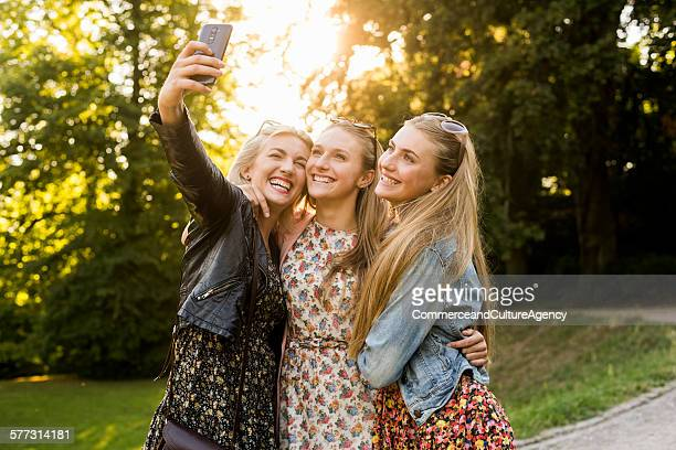 Smiling women taking selfie together outdoors