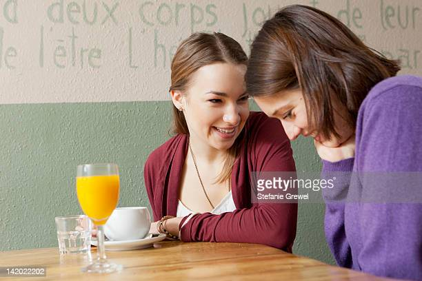 smiling women talking in cafe - stefanie grewel stock-fotos und bilder