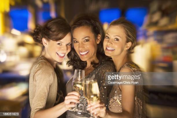 Verres de champagne toast souriant femmes dans un night-club