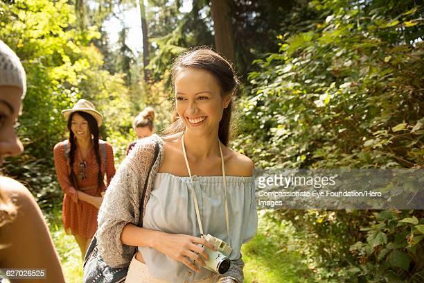 Smiling women walking in forest