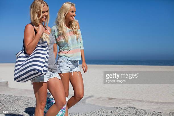 Smiling women walking together on beach