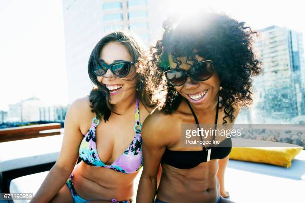 Smiling women wearing bikinis at urban poolside