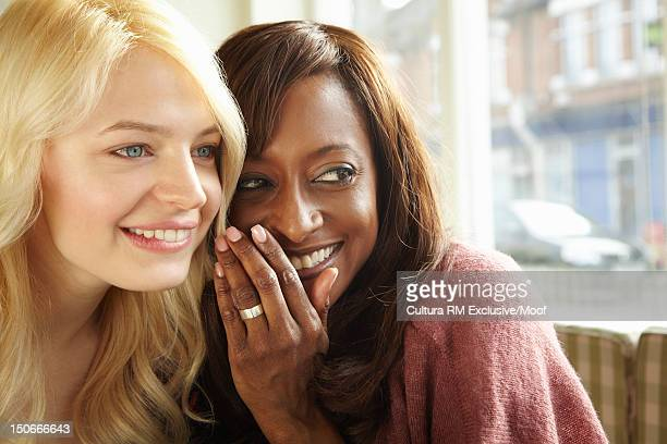 Smiling women whispering in cafe