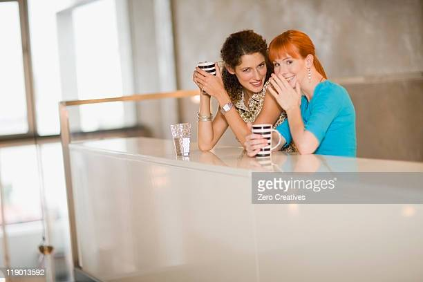 Smiling women whispering together