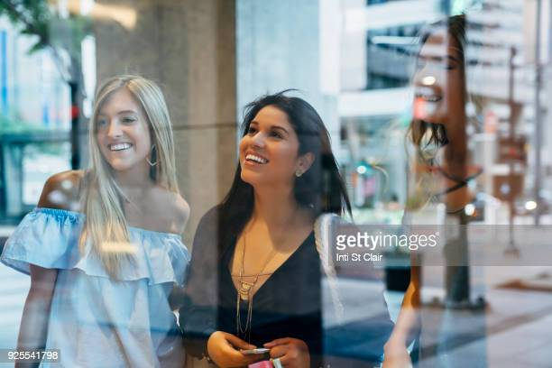 Smiling women window shopping