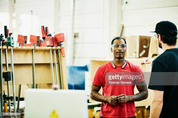 Smiling woodworker in discussion with coworker in cabinet shop
