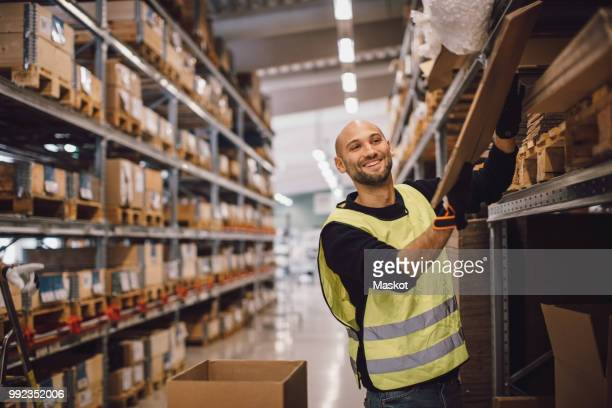 smiling worker checking wooden plank while standing in aisle at warehouse - construction material stock pictures, royalty-free photos & images